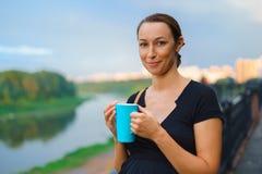 La fille se tient dehors avec la tasse bleue Images libres de droits