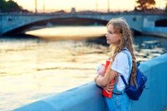 La fille se tient près de la rivière dans la ville au coucher du soleil image stock