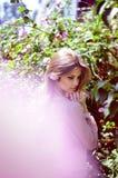 La fille se tient près des roses de thé de buisson Photographie stock libre de droits
