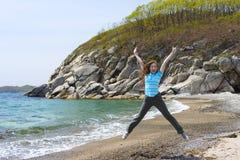 La fille se tient sur la pierre de mer Image libre de droits