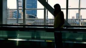 La fille se tient sur le passage couvert automatique dans le croisement de souterrain et parle au téléphone Le trafic se déplace  banque de vidéos