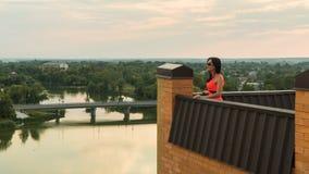 La fille se tient sur le toit d'une Chambre Le coucher du soleil image libre de droits