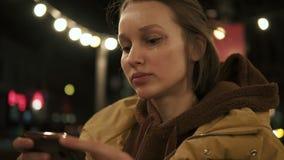 La fille se tient sur la rue regardant dans le petit miroir débourrent ses cheveux légers Étincelles sur son visage Temps de soir banque de vidéos