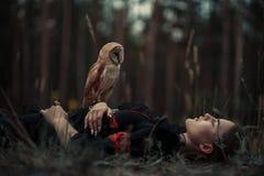 La fille se trouve avec le hibou sur l'herbe dans la forêt image stock