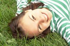 La fille se trouve sur l'herbe Photographie stock libre de droits