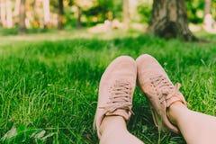 La fille se trouve sur l'herbe verte et ses jambes avec les chaussures s de rose Photographie stock libre de droits