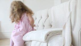 La fille se trouve sur le divan et se lève et  banque de vidéos