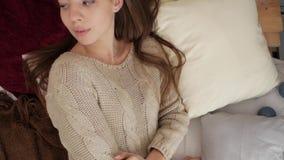 La fille se trouve sur le lit sur le fond de l'arbre de Noël An neuf banque de vidéos