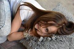 La fille se trouve sur le plancher photographie stock libre de droits