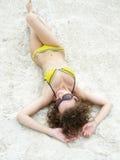 La fille se trouve sur le sable Photographie stock libre de droits