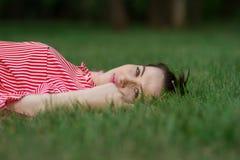 La fille se trouve sur une pelouse Image stock