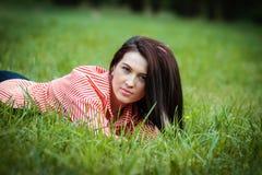 La fille se trouve sur une pelouse Image libre de droits