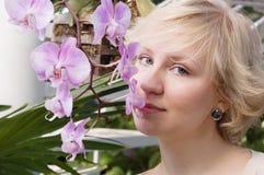 La fille sent une orchidée Photographie stock libre de droits