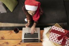 La fille seule dans un chapeau de Noël faisant des emplettes en ligne, utilise un ordinateur portable image stock