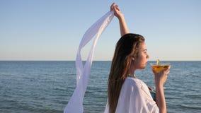 La fille sexuelle dans le contre-jour sur la plage, jeune femelle boit le cocktail banque de vidéos