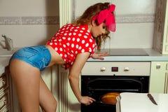 La fille avec du charme fait le pain cuire au four dans la pince à linge vers le haut du style Photographie stock