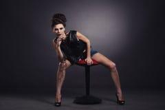 La fille sexy créative dans un gilet noir s'assied Photographie stock libre de droits