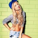 La fille sexy de bronzage dans des jeans courts court-circuite contre le mur de briques vert Photographie stock libre de droits
