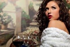 La fille sexy s'asseyent avec du vin dans le manteau de fourrure à la soirée Photo stock