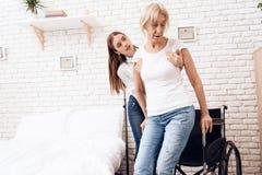 La fille soigne la femme agée à la maison La fille aide la femme à entrer dans le fauteuil roulant photo stock