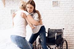 La fille soigne la femme agée à la maison La fille aide la femme à entrer dans le fauteuil roulant photos stock