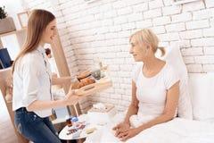 La fille soigne la femme agée à la maison La fille apporte le petit déjeuner sur le plateau photo libre de droits
