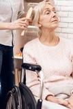 La fille soigne la femme agée à la maison La fille balaye des cheveux du ` s de femme images stock