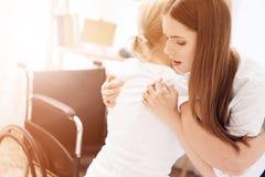 La fille soigne la femme agée à la maison La femme a besoin de l'aide entrer dans le fauteuil roulant photo stock