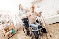 La fille soigne la femme agée à la maison La femme essaye de se lever du fauteuil roulant image libre de droits