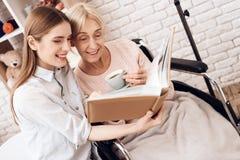 La fille soigne la femme agée à la maison Ils regardent des photos dans l'album photos photos stock