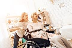 La fille soigne la femme agée à la maison La fille monte la femme dans le fauteuil roulant image libre de droits