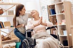 La fille soigne la femme agée à la maison La fille monte la femme dans le fauteuil roulant La femme s'amuse image stock
