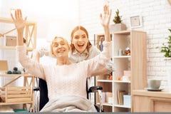 La fille soigne la femme agée à la maison La fille monte la femme dans le fauteuil roulant dans le salon photographie stock libre de droits