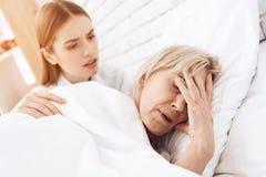 La fille soigne la femme agée à la maison La femme se sent mal, fille est concernée images stock