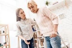 La fille soigne la femme agée à la maison La femme se tient avec l'aide du marcheur images stock