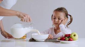 La fille somnolente commence à manger ses cornflakes avec du lait pour le petit déjeuner banque de vidéos