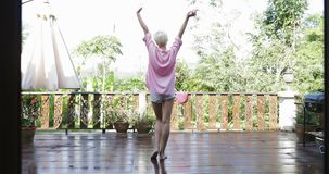 La fille sortent à la terrasse étirant la vue arrière de bras de retour, femme blonde apprécient la vue de matin de la forêt trop banque de vidéos