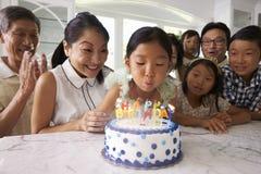 La fille souffle des bougies à la célébration d'anniversaire de famille Photographie stock libre de droits