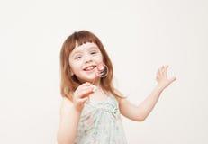 La fille souffle des bulles de savon sur le fond monophonique image libre de droits