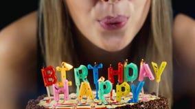 La fille souffle les bougies sur le gâteau, sourit banque de vidéos