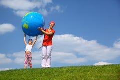 La fille soulève un globe vers le haut et des aides de mère Image stock