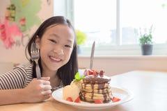 La fille sourit heureusement, tenant un couteau et la fourchette prépare pour manger des crêpes dans les restaurants image stock