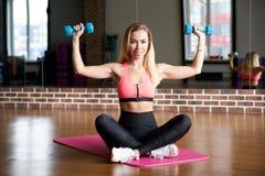 La fille sportive attirante dans les vêtements de sport est engagée dans le gymnase avec des haltères avec une expression satisfa Image stock
