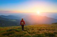 La fille sportive avec le sac arrière se tient à la pelouse et observe sur la fonte sans fin du paysage de montagnes Image libre de droits
