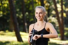 La fille sportive avec les sports observent photos stock