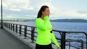 La fille sportive de brune en tissu de sport court sur le remblai écoutant la musique clips vidéos