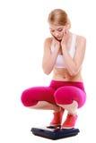 La fille sportive de femme de forme physique sur l'échelle s'est inquiétée avec son poids Photographie stock libre de droits