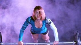 La fille sportive fait des pousées avec un barbell, la nuit, dans la fumée légère, brouillard, à la lumière des projecteurs multi clips vidéos