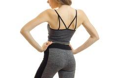 La fille sportive mince dans le costume gris de sports pose sur l'appareil-photo tournant vers l'arrière et garde ses mains des c Photos stock