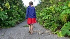 La fille suit la route abandonnée envahie par la berce banque de vidéos